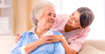 caregiver holding the hands of elderly patient