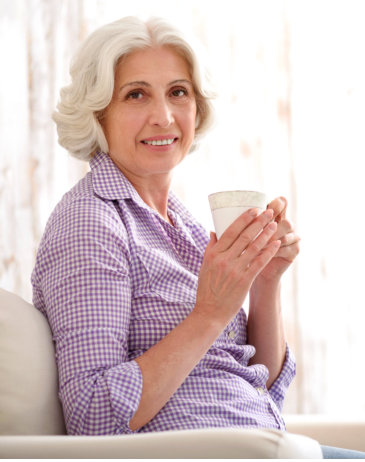 senior patient holding a cup