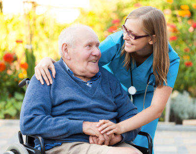 caregiver holding the hands of patient in a wheelchair