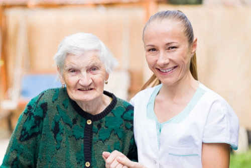 elderly woman with white hair and her caregiver smiling