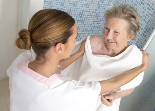 senior woman taking a bath with her caregiver